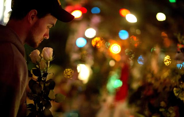 A Newtown resident who identified himself only as Andrew, holds roses as he visits a memorial for the Sandy Hook Elementary School shooting victims, Tuesday, Dec. 18, 2012, in Newtown, Conn. (AP Photo/David Goldman)
