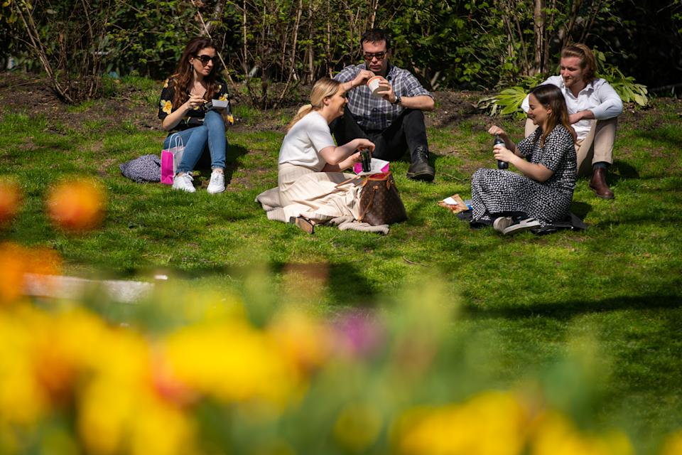 People enjoy their lunch in the sun at the Victoria Embankment Gardens in Central Lodnon. Picture date: Tuesday March 30, 2021. Temperatures in parts of the UK are expected to be significantly warmer this week as families and friends are reunited and sporting activities are allowed to resume in England.