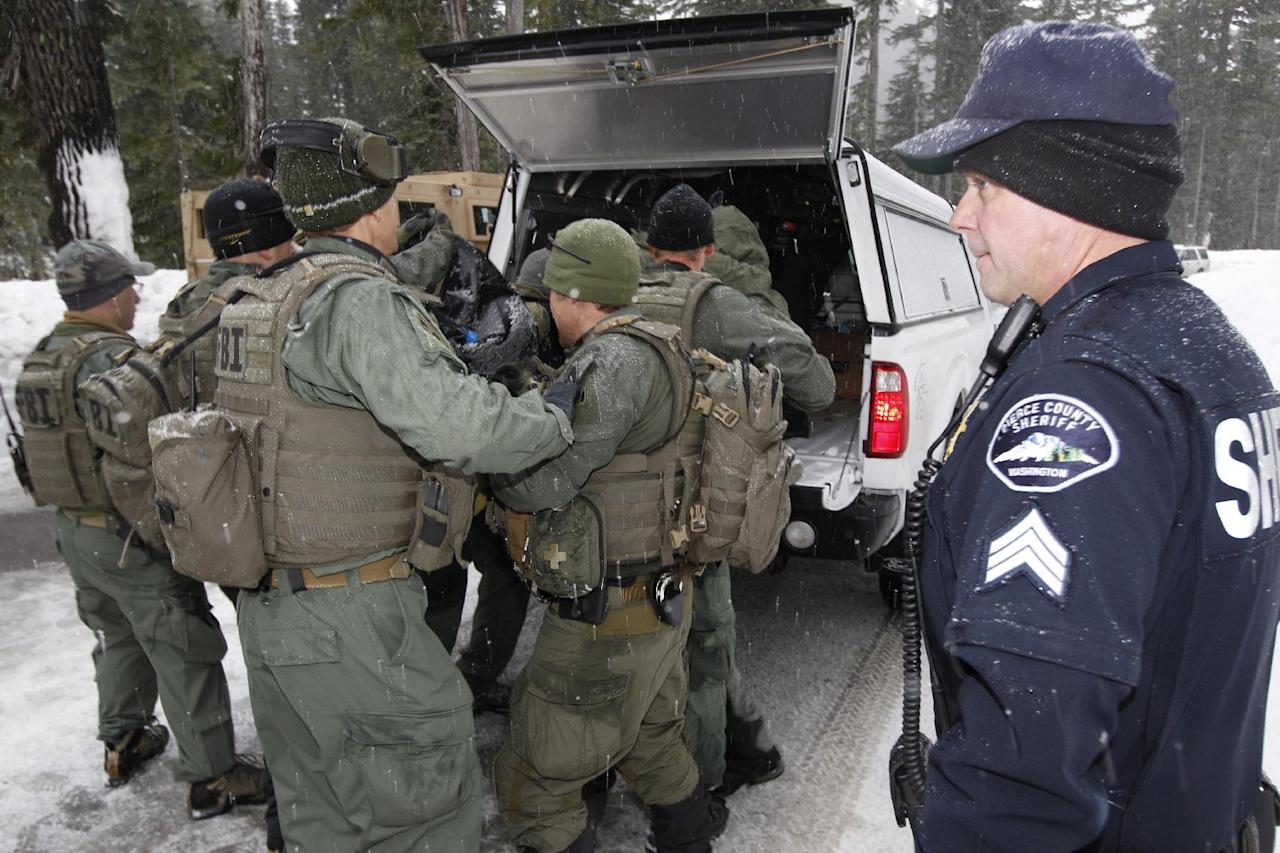 In this photo provided by the Pierce Co. Sheriff's Dept., Pierce County Sgt. Nick Hausner, right, looks on as FBI SWAT team members load the body of Benjamin Colton Barnes into a vehicle Monday, Jan. 2, 2012, at Mount Rainier National Park in Washington state. Barnes' body was recovered from a creek bed Monday, after he allegedly shot and killed a park ranger Sunday during a traffic stop in the park. Barnes did not have any external wounds and appears to have died due to the elements, Sheriff's spokesman Ed Troyer said. (AP Photo/Pierce Co. Sheriff's Dept., Ed Troyer, Pool)