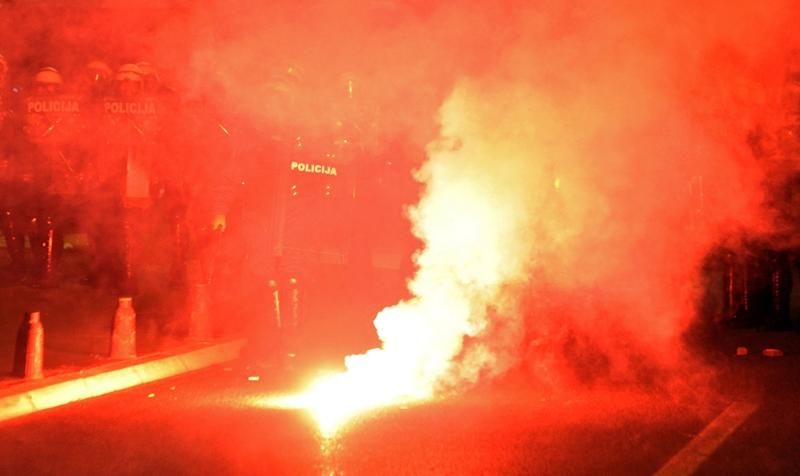 Montenegro's opposition protesters throw flares at police officers in capital Podgorica on October 18, 2015