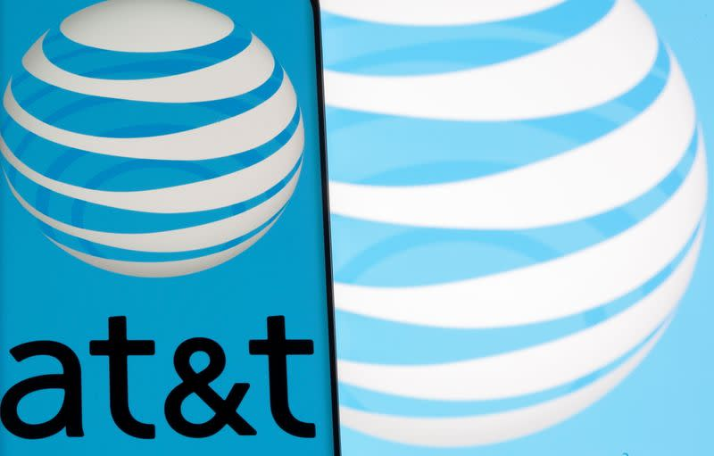 AT&T logo is seen on a smartphone in front of displayed same logo in this illustration