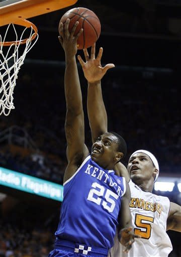Kentucky's Marquis Teague (25) puts up a shot past Tennessee's Jarnell Stokes (5) in the second half of an NCAA college basketball game on Saturday, Jan. 14, 2012, in Knoxville, Tenn. Kentucky won 65-62. (AP Photo/Wade Payne)