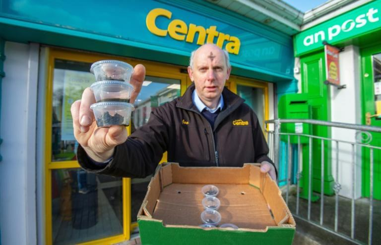 Joe Joyce poses with takeaway pots of ashes his shop produced for Ash Wednesday outside the Centra shop in Clonmany, County Donegal.
