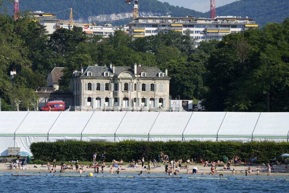 People swim on the shores of Lake Geneva in front of a tent that was set up as a media center opposite the 'Villa La Grange' the venue for the upcoming meeting between US President Joe Biden and Russian President Vladimir Putin, in Geneva, Switzerland Monday, June 14, 2021. The lakeside city known as a Cold War crossroads and a hub for Swiss discretion, neutrality and humanitarianism, is set to return to a spotlight on the world stage as U.S. President Joe Biden and Russian President Vladimir Putin come to town for a summit on Wednesday, June 16.(AP Photo/Markus Schreiber)