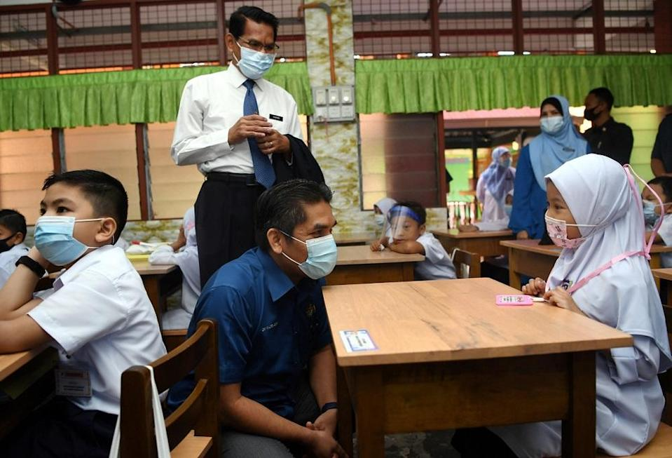 Senior Education Minister Datuk Radzi Jidin (centre) speaks to a student during his visit to Sekolah Kebangsaan King George V in Seremban March 8, 2021. — Bernama pic