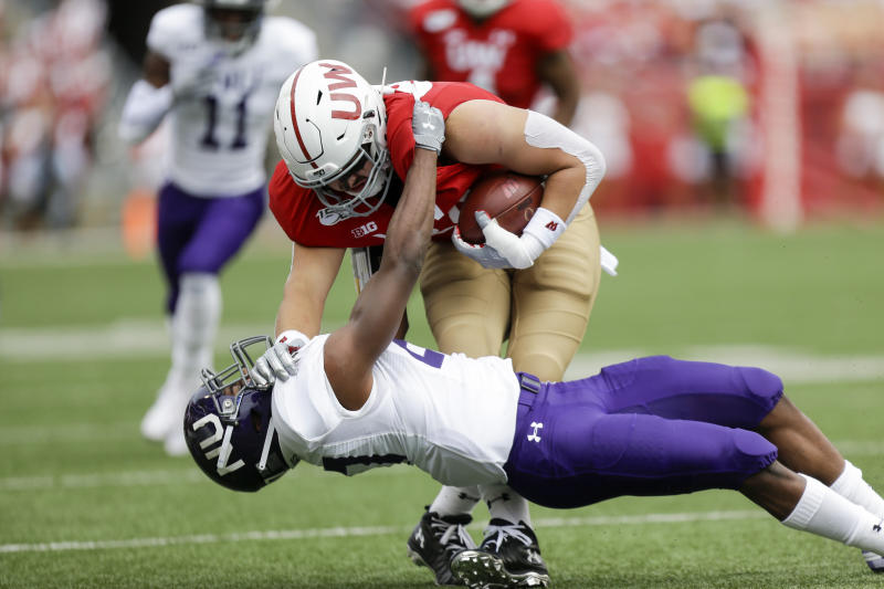 Northwestern defensive back Coco Azema (27) tackles Wisconsin tight end Jake Ferguson (84) during the first half of an NCAA college football game Saturday, Sept. 28, 2019, in Madison, Wis. (AP Photo/Andy Manis)