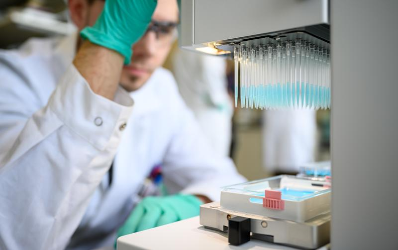 """24 February 2020, Baden-Wuerttemberg, Tübingen: A man pipettes a blue liquid in a laboratory of the biopharmaceutical company Curevac. (to dpa: """"Tübingen company tinkering with the enemy's profile"""") Photo: Sebastian Gollnow/dpa (Photo by Sebastian Gollnow/picture alliance via Getty Images)"""