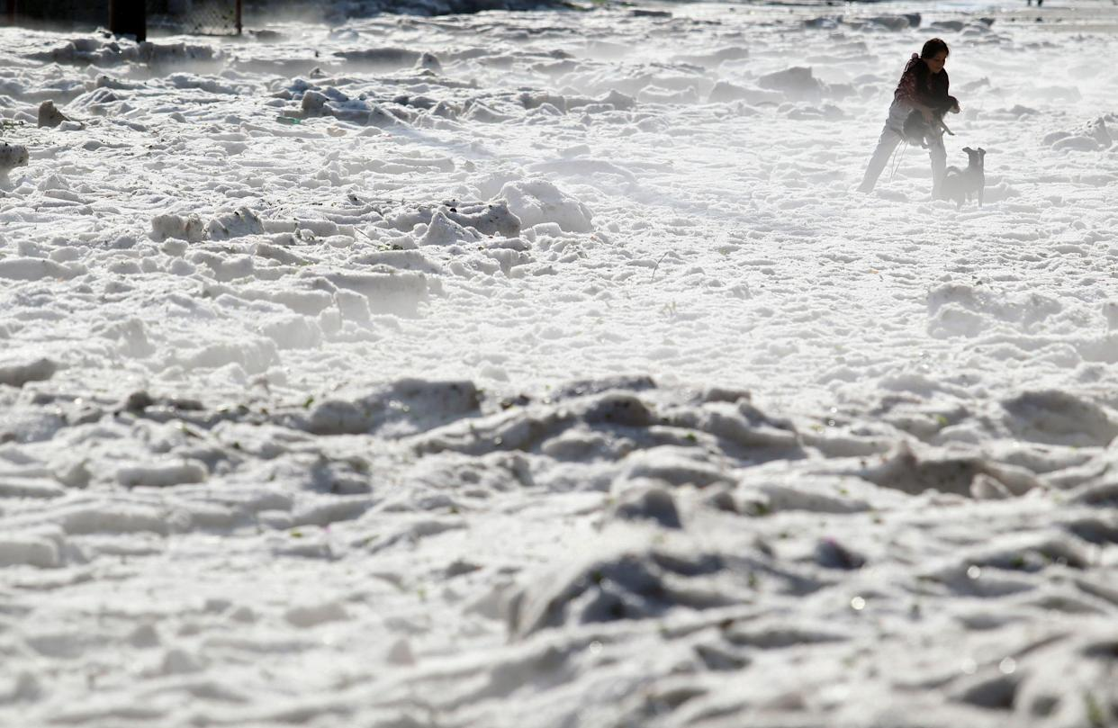 A woman and her dogs walk on hail in Guadalajara, Mexico, on June 30. (Photo: Ulisies Ruiz/AFP/Getty Images)