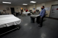 Owner Brian Simmons looks over the preparation room in mortuary as workers get ready to prepare a body Thursday, Jan. 28, 2021, in Springfield, Mo. Simmons has been making more trips to homes to pick up bodies to be cremated and embalmed since the pandemic hit. For many families, home is a better setting than the terrifying scenario of saying farewell to loved ones behind glass or during video calls amid the coronavirus pandemic. (AP Photo/Charlie Riedel)