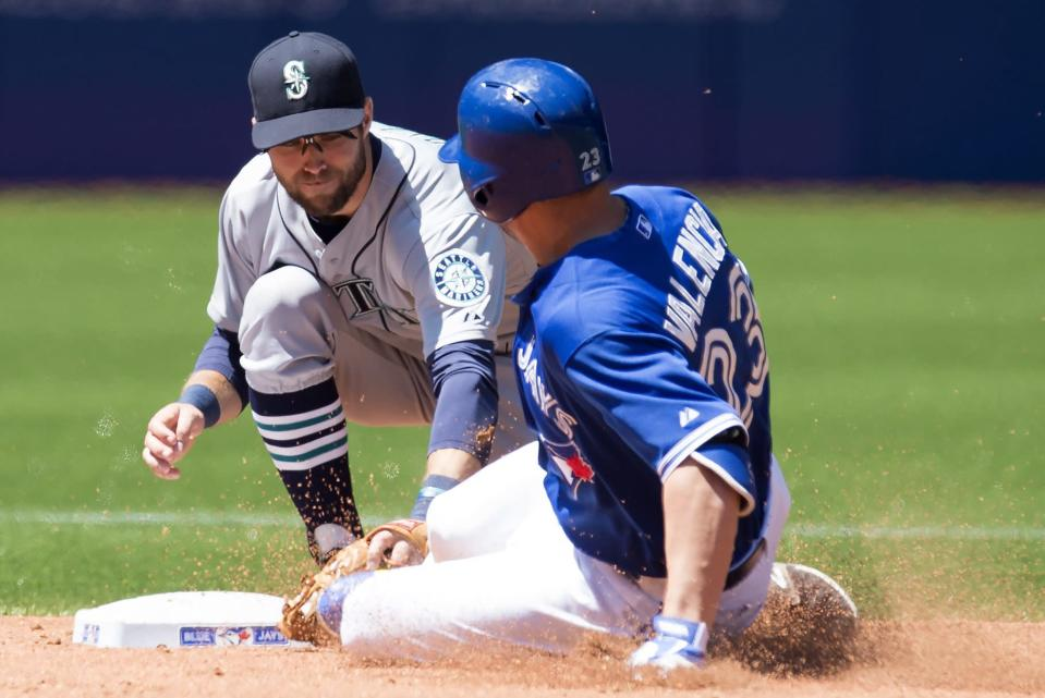 Toronto Blue Jays' Danny Valencia(23) is tagged out by Seattle Mariners shortstop Chris Taylor while trying to stretch a single into a double during fourth inning AL action in Toronto on Saturday, May 23, 2015. (Frank Gunn/The Canadian Press via AP) MANDATORY CREDIT