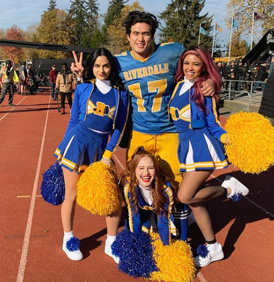 A photo of Camila Mendes, Charles Melton, Madelaine Petsch and Vanessa Morgan wearing yellow and blue sports uniforms on the set of Riverdale.