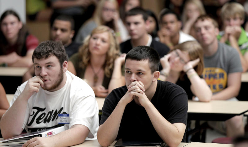 FILE - In this Wednesday, Aug.  17, 2011 file photo, students listen during an assembly on the first day of school at a temporary high school in a converted store in Joplin, Mo., nearly three months after an EF-5 tornado destroyed six schools and damaged four others along with killing 160 people and devastating a third of the city. According to research cited in a report by the federal Agency for Healthcare Research and Quality, about two-thirds of U.S. children and teens younger than 18 will experience at least one traumatic event, including shootings and other violence, car crashes and weather disasters. (AP Photo/Charlie Riedel)
