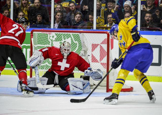 Switzerland's goalie Melvin Nyffeler tries to save a shot from Sweden's Oskar Sundqvist (R) during the first period of their IIHF World Junior Hockey Championship ice hockey game in Malmo December 26, 2013. REUTERS/Ludvig Thunman/TT News Agency (SWEDEN - Tags: SPORT ICE HOCKEY) ATTENTION EDITORS - THIS IMAGE WAS PROVIDED BY A THIRD PARTY. THIS PICTURE IS DISTRIBUTED EXACTLY AS RECEIVED BY REUTERS, AS A SERVICE TO CLIENTS. SWEDEN OUT. NO COMMERCIAL OR EDITORIAL SALES IN SWEDEN. NO COMMERCIAL SALES
