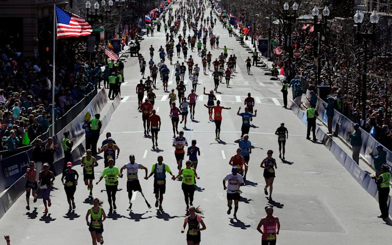 Runners approach the finish line of the 120th Boston Marathon in Boston last year - Credit: AP