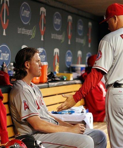 Los Angeles Angels pitching coach Mike Butcher, right, talks to starting pitcher Jered Weaver in the dugout after Weaver gave up a hit in the third inning against the Minnesota Twins, Monday, May 7, 2012, in Minneapolis. This is Weaver's first start after no-hitting the Twins and becomes the first pitcher since Derek Lowe in 2002 to face the same team in his next start. (AP Photo/Genevieve Ross)