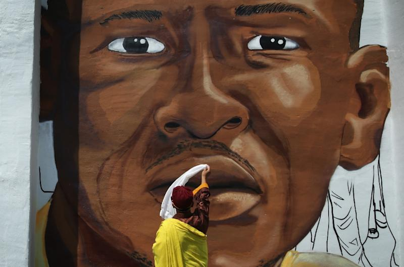 A South Asian Buddhist leader waves a scarf in front of a mural of Freddie Gray as he tours the Sandtown neighborhood May 7, 2015 in Baltimore, Maryland (AFP Photo/Alex Wong)