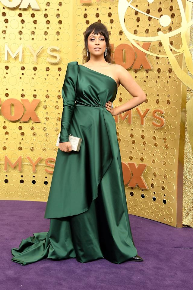 Emerald is everything tonight, and Lilly Singh's ensemble is no exception. In a perfectly draped floor-length gown with a dramatic one-shoulder neckline, Lilly accessorized with a golden box clutch and coordinating rings.