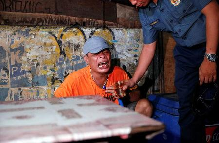 A police officer gives a glass of water to a man as he comforts him after his brother, who police say was killed in a spate of drug-related violence overnight, was shot in Manila, Philippines August 16, 2017.   REUTERS/Dondi Tawatao