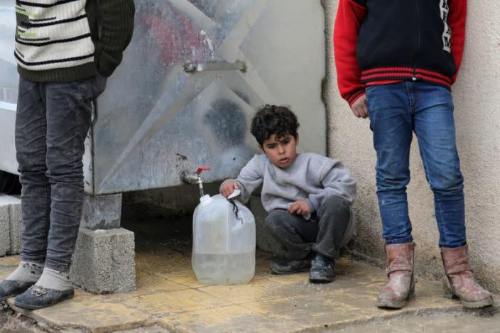Internally displaced child fills a container with water in Azaz