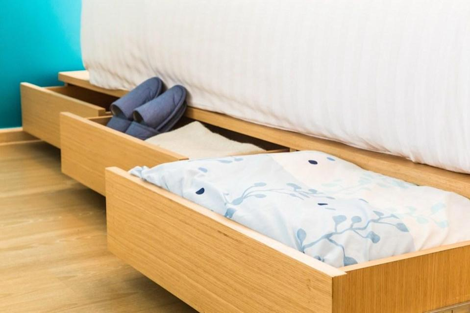 """Don't sleep on under-bed storage: <span>If you have a small bedroom, it's key. Let's say you're working with a queen-sized bed. By investing in an under-bed storage solution </span><span>you'll fabricate out of thin air about 35 square feet of storage space. Consider picking up a bed platform with built-in drawers. Or, if you're looking to cut costs, pick up <a rel=""""nofollow noopener"""" href=""""https://amzn.to/2RGkwWk"""" target=""""_blank"""" data-ylk=""""slk:a set of nondescript bed risers ($22)"""" class=""""link rapid-noclick-resp"""">a set of nondescript bed risers ($22)</a> and <a rel=""""nofollow noopener"""" href=""""https://fave.co/2RywcdM"""" target=""""_blank"""" data-ylk=""""slk:actually stylish under-bed storage boxes ($13)"""" class=""""link rapid-noclick-resp"""">actually stylish under-bed storage boxes ($13)</a>.</span>"""