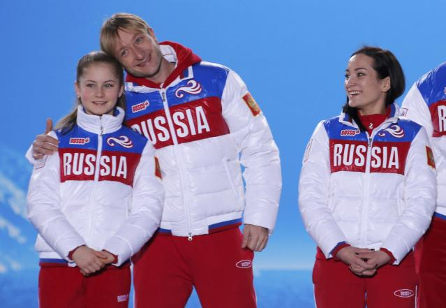 The gold medal-winning Russian figure skating team pose for a photo during the medal ceremony for the figure skating team ice dance free dance at the Sochi 2014 Winter Olympics February 10, 2014. From L to R: Yulia Lipnitskaya, Evgeny Plyushchenko, Ksenia Stolbova. REUTERS/David Gray (RUSSIA - Tags: OLYMPICS SPORT FIGURE SKATING)