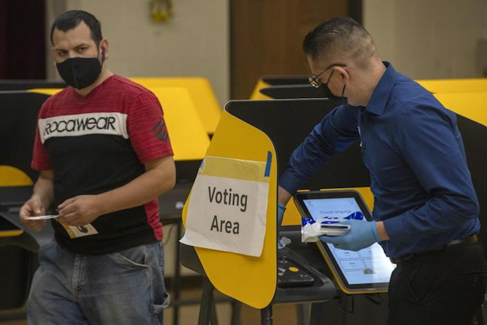 A poll worker, right, sanitizes a voting machine