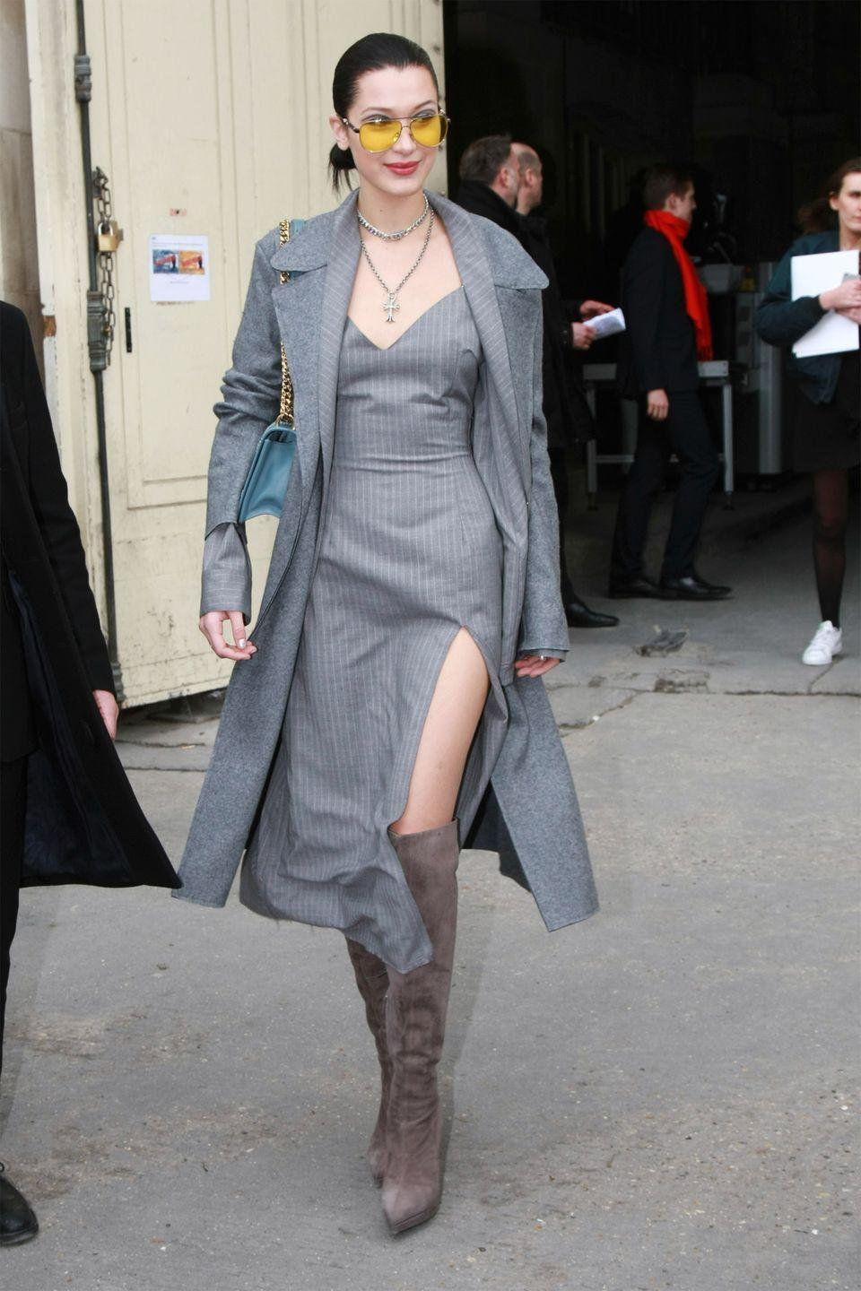 <p>In a pinstripe Baja East slip dress and DSTLD wool blanket maxi coat with knee-high grey suede boots by Giuseppe Zanotti and yellow aviator sunglasses while leaving the Chanel show in Paris. </p>