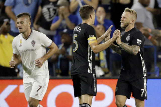 Sporting Kansas City defender Matt Besler (5) and forward Johnny Russell (7) celebrate after Colorado Rapids defender Tommy Smith kicked the ball into his own goal to score a Sporting Kansas City goal during the first half of an MLS soccer match Saturday, Sept. 21, 2019, in Kansas City, Kan. (AP Photo/Charlie Riedel)