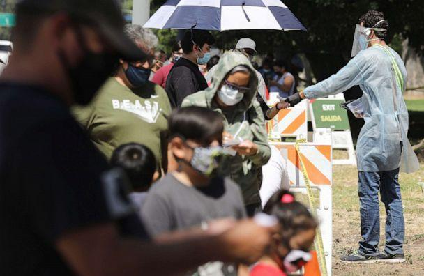 PHOTO: A testing associate dressed in personal protective equipment helps people waiting in line to check in at a COVID-19 testing center at Lincoln Park amid the coronavirus pandemic on July 07, 2020, in Los Angeles. (Mario Tama/Getty Images)