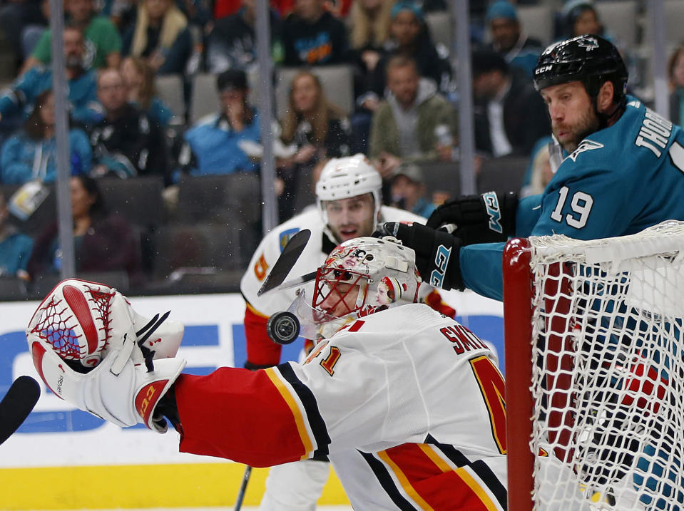 Calgary Flames goaltender Mike Smith (41) makes a save against San Jose Sharks' Joe Thornton (19) in the second period of an NHL hockey game in San Jose, Calif., Sunday, Nov. 11, 2018. (AP Photo/Josie Lepe)