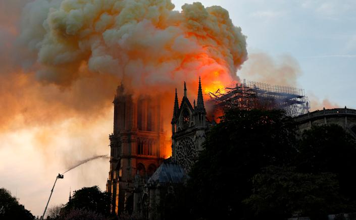 A firefighter uses a hose to douse flames and smoke billowing from the roof at Notre-Dame Cathedral in Paris on April 15, 2019. (Photo: Geoffroy Van Der Hasselt/AFP/Getty Images)