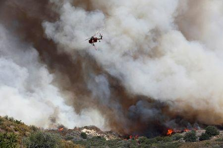 A firefighting helicopter passes over the so-called Sand Fire in the Angeles National Forest near Los Angeles, California, U.S. July 24, 2016. REUTERS/Jonathan Alcorn