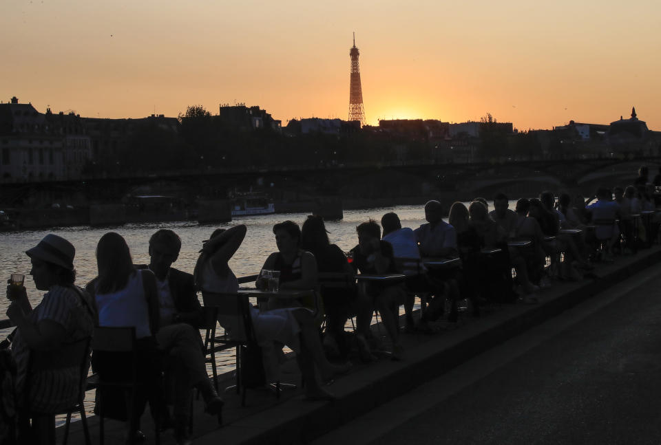 "People enjoy drinks along the Seine river bank duringsun set in Paris, Thursday, Sept. 17, 2020. Health Minister Olivier Veran announced 20 more testing centers nationwide as he told a press conference that the virus is ""very active again"" in France. Eiffel Tower in the background. (AP Photo/Michel Euler)"