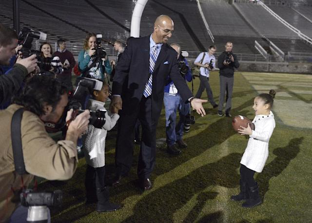 Penn State's new football coach James Franklin prepares to catch a football from his daughter, Addison, 5, after being introduced during an NCAA college football news conference at Beaver Stadium, Saturday, Jan. 11, 2014, in State College, Pa. Holding her father's hand is Shola, 6. (AP Photo/John Beale)