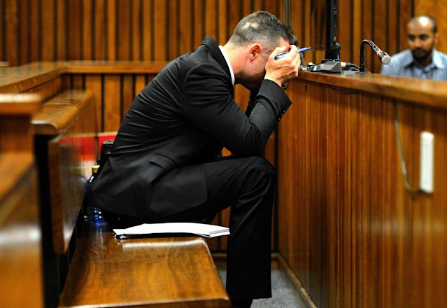 Oscar Pistorius, cradles his head in his hands during court proceedings in Pretoria, South Africa, Monday May 5, 2014 at the resumption of his murder trial, following a two week break. Pistorius is charged with the shooting death of his girlfriend Reeva Steenkamp on Valentine's Day in 2013. (AP Photo/Thobile Mathonsi, Pool)