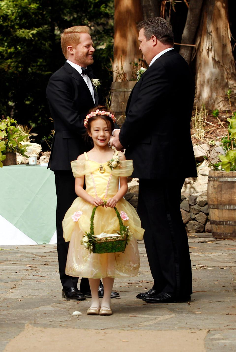 """Aubrey Anderson-Emmons, Jesse Tyler Ferguson and Eric Stonestreet in season five of """"Modern Family,"""" in which Mitch and Cam got married with their daughter, Lily, serving as flower girl."""