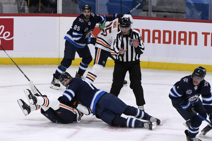 Winnipeg Jets' Adam Lowry (17) becomes entangled with Edmonton Oilers' Kyle Turris after a faceoff during the first period of an NHL hockey game Tuesday, Jan. 26, 2021, in Winnipeg, Manitoba. (Fred Greenslade/The Canadian Press via AP)