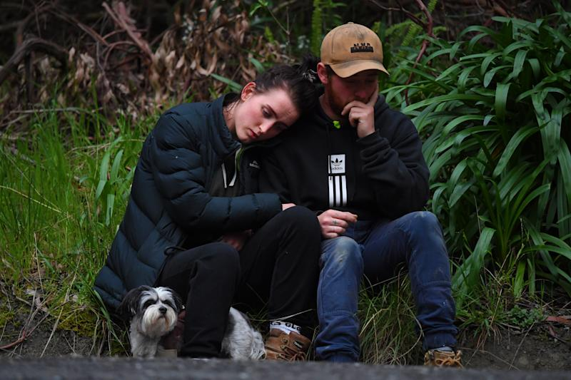 Two people sit on the roadside after the discovery of William's body. Source: AAP