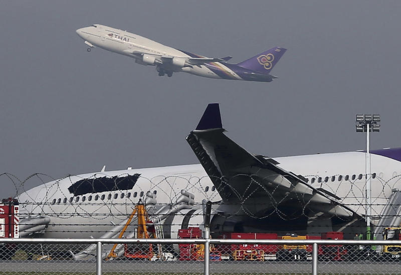 A Thai Airways passenger plane takes off over a damaged Thai Airways Airbus A330-300 at Suvarnabhumi International Airport in Bangkok, Thailand, Monday, Sept. 9, 2013. The plane carrying more than 280 people skidded off the runway while landing at the airport Sunday, injuring 14 passengers. (AP Photo/Apichart Weerawong)
