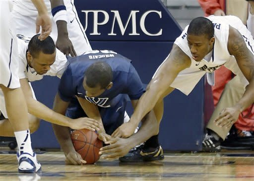 Villanova's Daniel Ochefu, center, tries to keep a loose ball from Pittsburgh's Trey Zeigler, left, and Lamar Patterson, right, in the first half of an NCAA college basketball game on Sunday, March 3, 2013, in Pittsburgh. (AP Photo/Keith Srakocic)