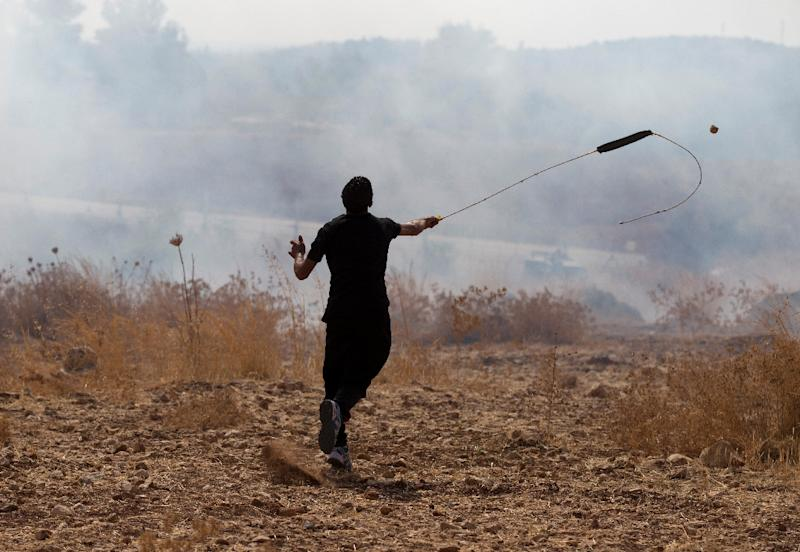 A Palestinian demonstrator throws a stone using a sling shot towards Israeli security forces during clashes in the West Bank village of Budrus, west of Ramallah (AFP Photo/Abbas Momani)