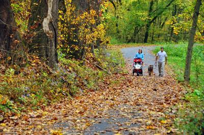A family walks along the Mon River Trail at Pricketts Fort in West Virginia. The 48-mile Mon River Rail-Trail System, comprising the Mon River, Caperton and Deckers Creek Trails that converge in Morgantown, is the 2020 inductee to Rails-to-Trails Conservancy's Rail-Trail Hall of Fame. Photo by Steve Shaluta, courtesy Mon River Trails Conservancy.