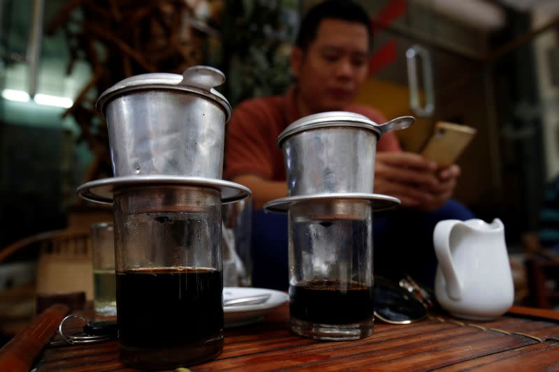 A man waits for coffee to brew at a cafe in Hanoi