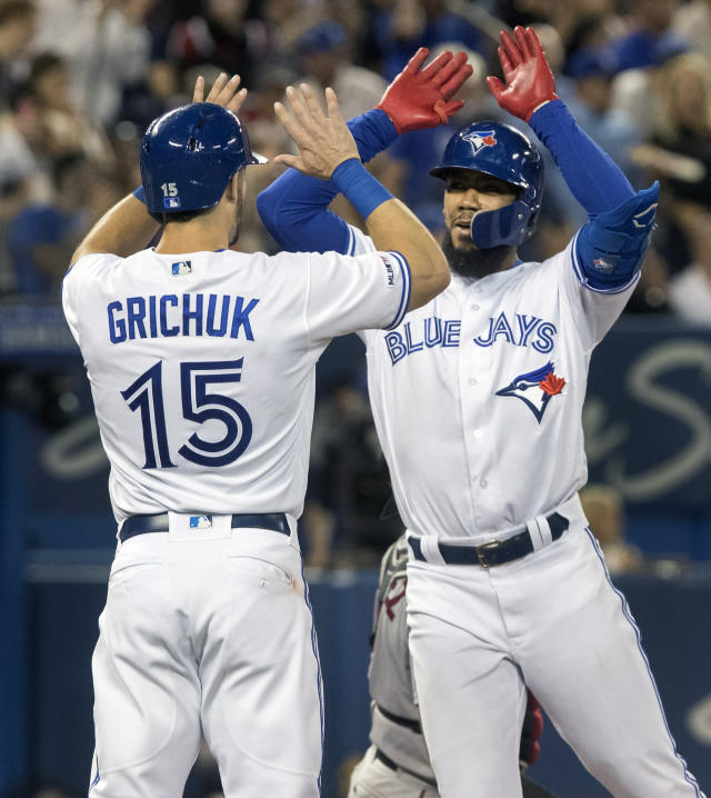 Toronto Blue Jays' Teoscar Hernandez, right, high fives with teammate Randal Grichuk after hitting a two-run home run against the Boston Red Sox during the fifth inning of a baseball game, Wednesday, Sept. 11, 2019 in Toronto. (Fred Thornhill/The Canadian Press via AP)