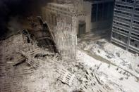 <p>A group of firefighters walk amid rubble near the base of the destroyed south tower of the World Trade Center. (Reuters)</p>