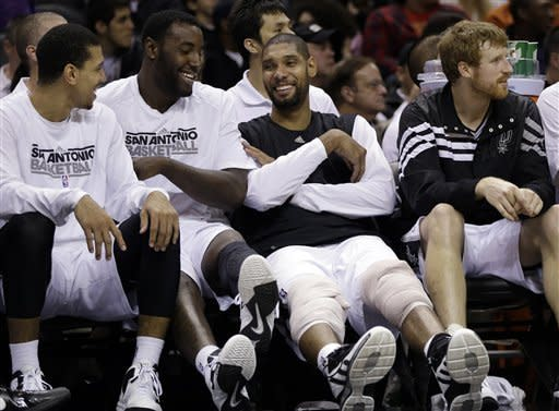 San Antonio Spurs' Tim Duncan, second from right, jokes with teammates, from left, Danny Green, DeJuan Blair, and Matt Bonner, right, as he ices his knees on the bench during the fourth quarter of an preseason NBA basketball game against the Washington Wizards, Friday, Oct. 26, 2012, in San Antonio. (AP Photo/Eric Gay)