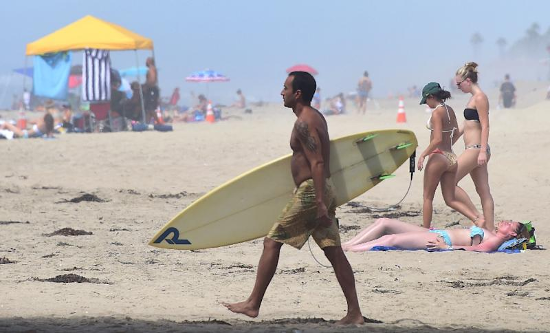 A surfer carries his board past sunbathers at Huntington Beach on September 10, 2015, amid a heat wave where temperatures have reached triple digits in parts of southern California (AFP Photo/Frederic J Brown )
