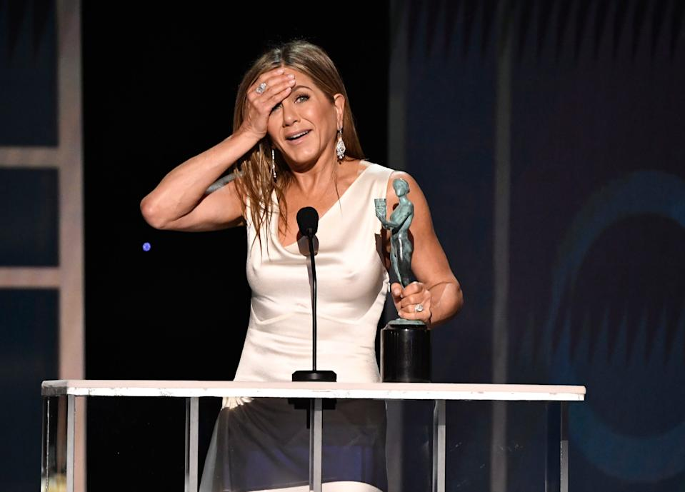 "An emotional Jennifer Aniston accepts the SAG award for female actor in a drama series for her role as Alex Levy in ""The Morning Show."""