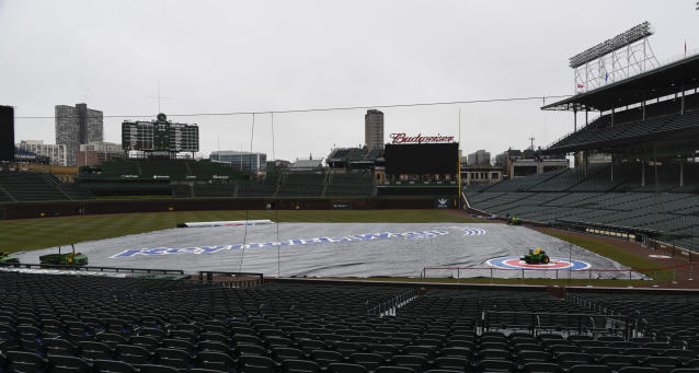 The tarp lays on Wrigley Field after a baseball game between the Atlanta Braves and the Chicago Cubs was postponed on Sunday, April 15, 2018, in Chicago. The game is rescheduled for Monday, May 14, 2018. (AP Photo/Matt Marton)