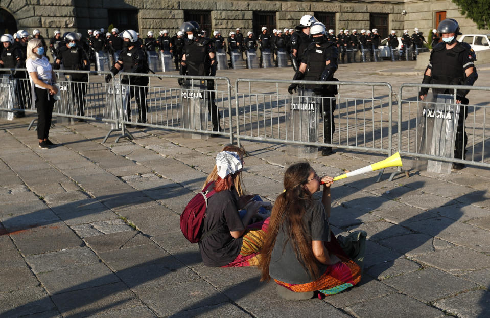 People sit on the ground as riot police guards the area in front of the Serbian Parliament building during a demonstration in Belgrade, Serbia, Wednesday, July 8, 2020. Serbia's president Aleksandar Vucic backtracked Wednesday on his plans to reinstate a coronavirus lockdown in Belgrade after thousands protested the move and violently clashed with the police in the capital. (AP Photo/Darko Vojinovic)